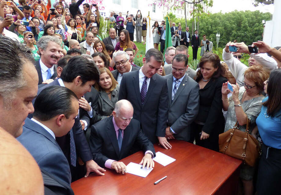 In this photo provided by the City of Los Angeles, California Gov. Jerry Brown signs a bill, Thursday Oct. 3, 2013 in Los Angeles, adding California to the growing list of states allowing immigrants living in the country illegally to obtain driver licenses. The licenses will carry a distinction on the front of the card and also state that it is not valid federal identification. (AP Photo/City of Los Angeles) / City of Los Angeles