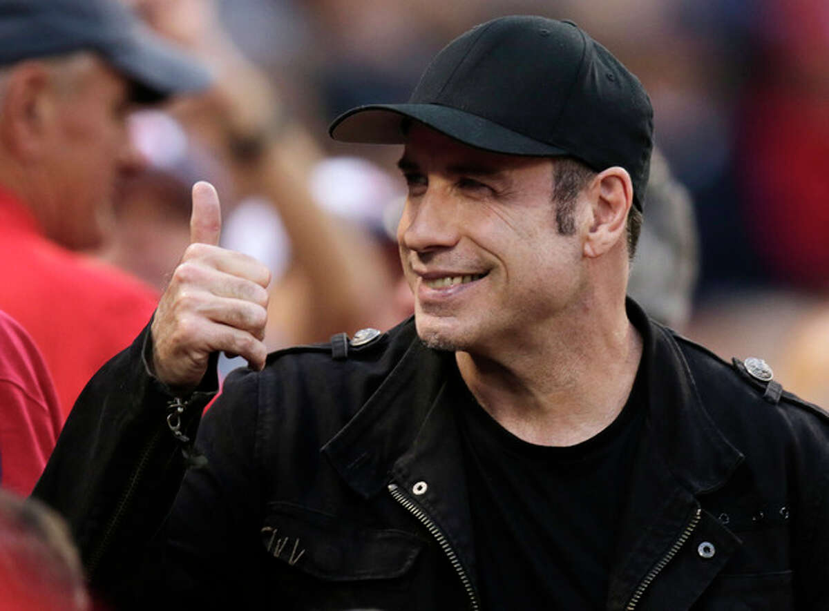 Actor John Travolta gives a thumbs-up to fans during the seventh inning in Game 1 of baseball's American League division series between the Boston Red Sox and the Tampa Bay Rays, Friday, Oct. 4, 2013, in Boston. (AP Photo/Charles Krupa)