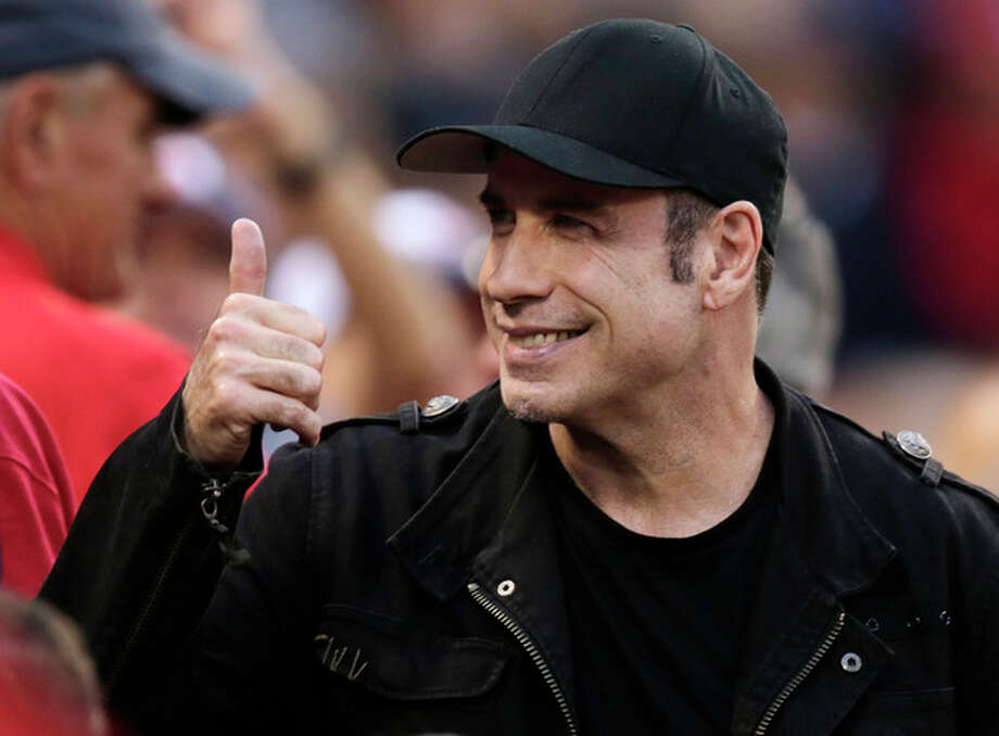 Actor John Travolta gives a thumbs-up to fans during the seventh inning in Game 1 of baseball's American League division series between the Boston Red Sox and the Tampa Bay Rays, Friday, Oct. 4, 2013, in Boston. (AP Photo/Charles Krupa) / AP