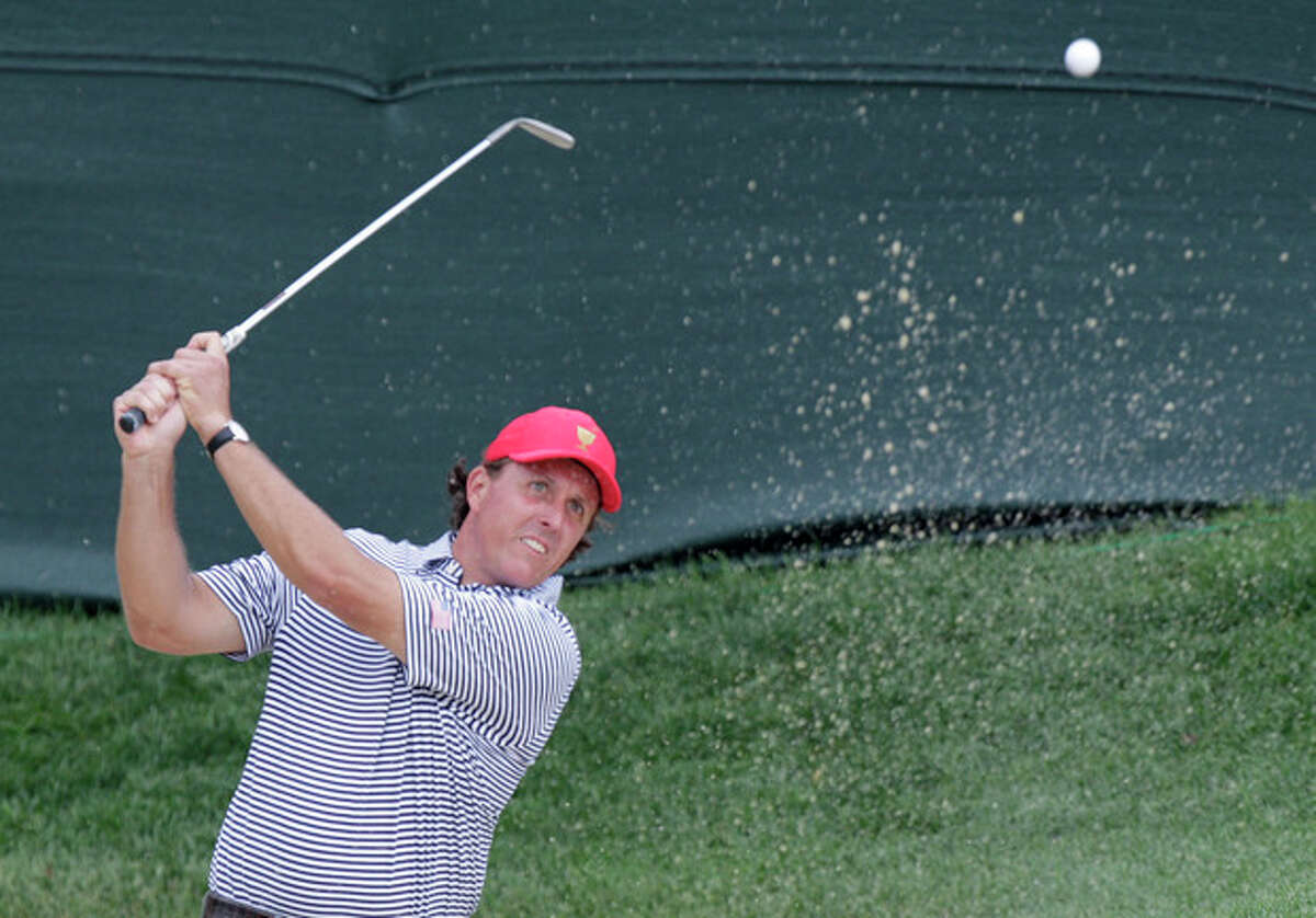 United States' Phil Mickelson hits from the sand on the first hole during a foursome match against the International team at the Presidents Cup golf tournament at Muirfield Village Golf Club Friday, Oct. 4, 2013, in Dublin, Ohio.