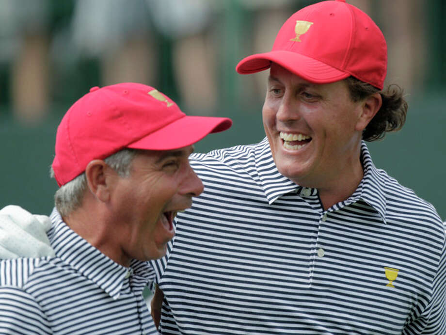 United States' Phil Mickelson, right, and team captain Fred Couples laugh together while walking down the first tee during a foursome match against the International team at the Presidents Cup golf tournament at Muirfield Village Golf Club Friday, Oct. 4, 2013, in Dublin, Ohio. (AP Photo/Jay LaPrete) / FR52593 AP