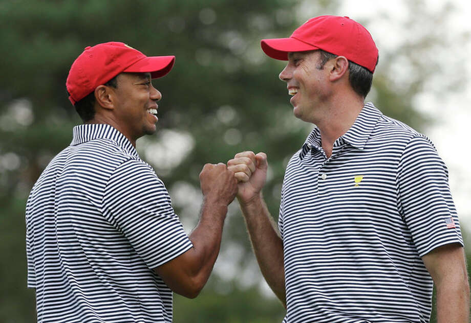 United States team player Tiger Woods, left, and team player Matt Kuchar fist bump after Kuchar made a birdie putt on the fourth hole during a foursome match at the Presidents Cup golf tournament at Muirfield Village Golf Club, Friday, Oct. 4, 2013, in Dublin, Ohio. (AP Photo/Darron Cummings) / AP