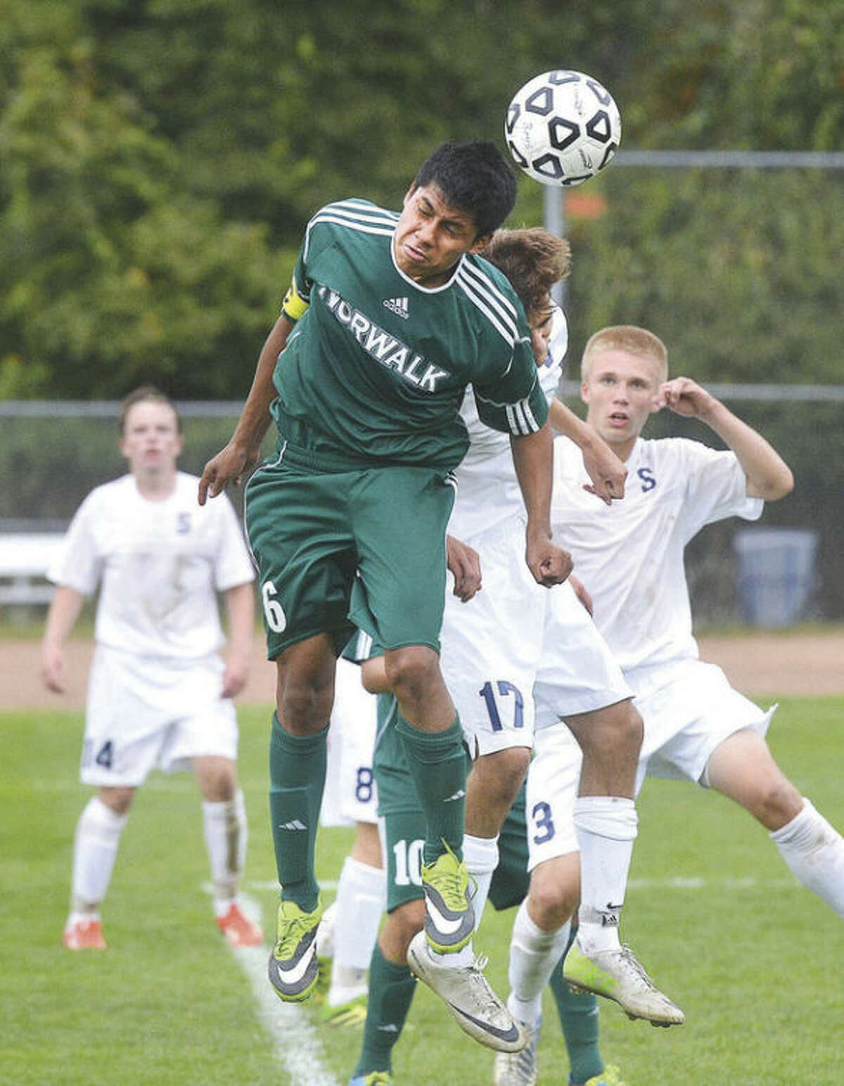 Hour Photo/Alex von Kleydorff Norwalk's Jose Canahui (6) and Staple's James Lewis (17) go for the ball during Thursday's FCIAC boys soccer game in Westport. The host Wreckers posted a 2-0 win over the Bears.