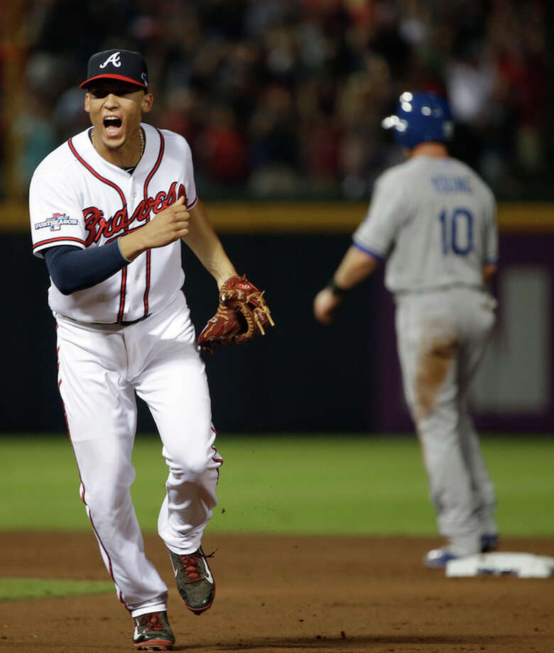 Atlanta Braves shortstop Andrelton Simmons, left, reacts after he turned a double play against the Los Angeles Dodgers in the seventh inning during Game 2 of the National League division series on Friday, Oct. 4, 2013, in Atlanta. (AP Photo/John Bazemore) / AP
