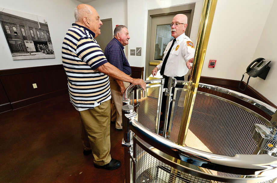 Hour photo / Erik Trautmann Chief Denis Mcarthy points out the poles to former Norwalk firefighters Joseph Ferraro and Julius Oraviz as the City of Norwalk and the Fire Department formally dedicate the new Central Fire Station Saturday.