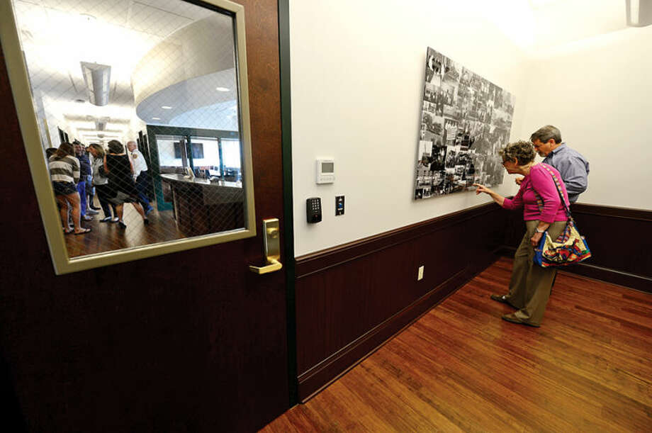 Hour photo / Erik Trautmann Steve Yost and his mother Fran Yost look for relatives in a photo collage on the 3rd floor of the new fire station as the City of Norwalk and the Fire Department formally dedicate the new Central Fire Station Saturday.