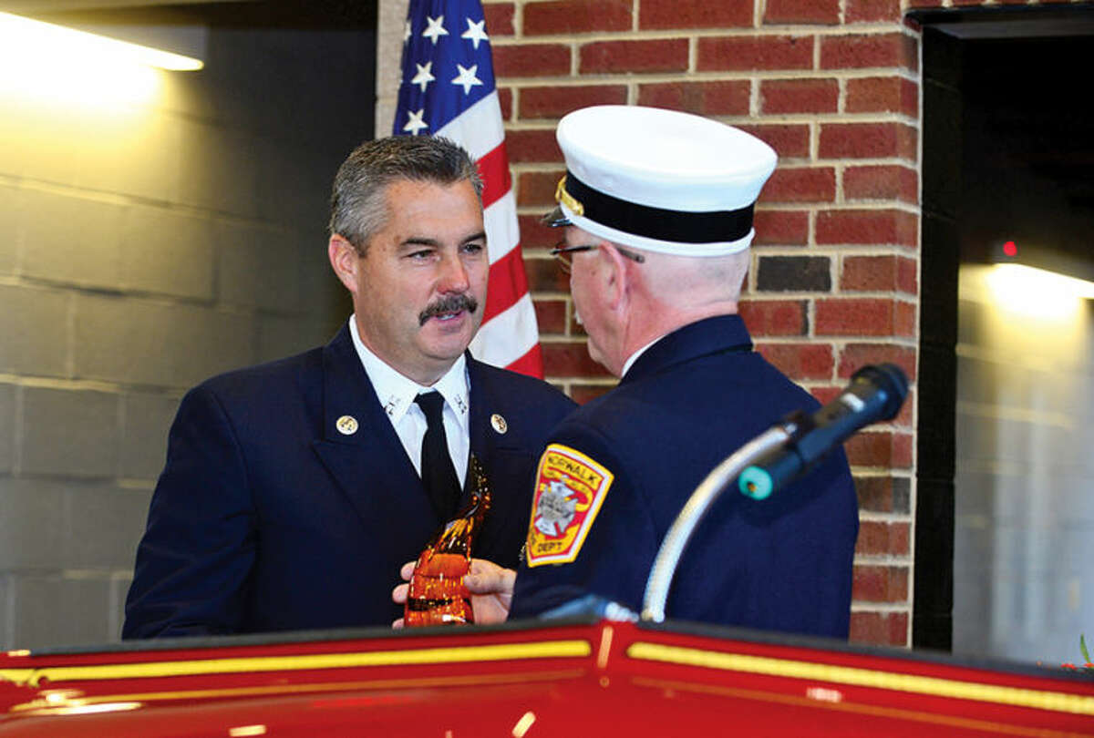 Hour photo / Erik Trautmann Norwalk Fire Chief Denis McCarthy recognizes Captain Jim Hines for his contributions as the City of Norwalk and the Fire Department formally dedicate the new Central Fire Station Saturday.