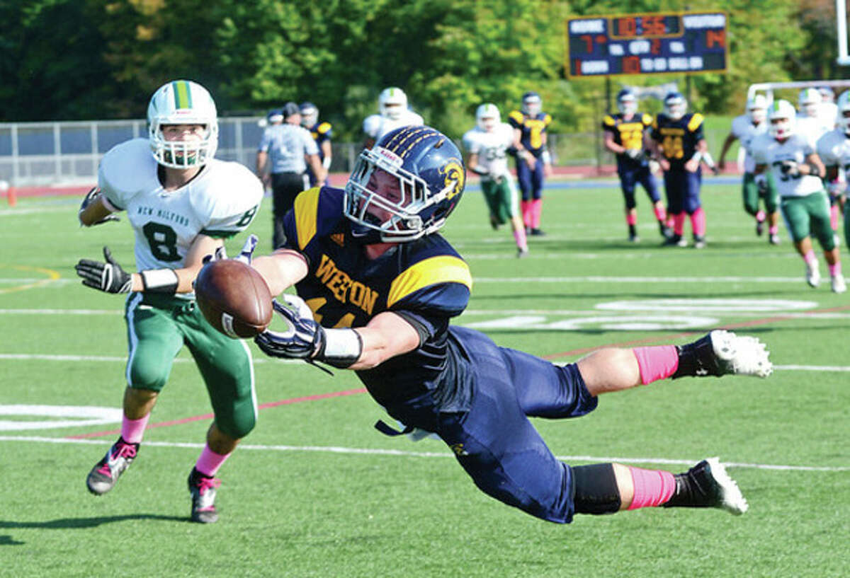 Hour photo/Erik Trautmann Weston's Peter Lummis goes all out as he tries to pull in a pass during Saturday's game against New Milford in Weston. Despite the effort, Lummis and the Trojans absorbed a 35-20 defeat.