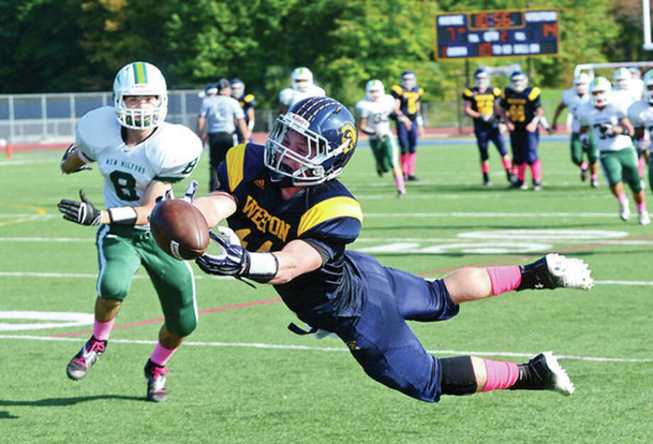 Hour photo/Erik TrautmannWeston's Peter Lummis goes all out as he tries to pull in a pass during Saturday's game against New Milford in Weston. Despite the effort, Lummis and the Trojans absorbed a 35-20 defeat. / (C)2013, The Hour Newspapers, all rights reserved