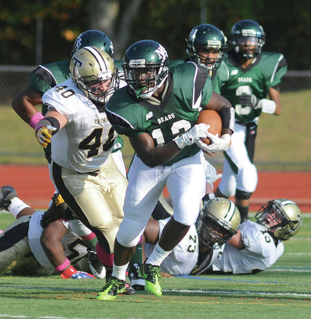 Hour photo/John Nash Under a bevy of eyes watching him, Norwalk's Clifford Joseph, center, runs away from blockers and tacklers alike while gaining some ground in the first quarter of Saturday's game against Trumbull at Testa Field in Norwalk.