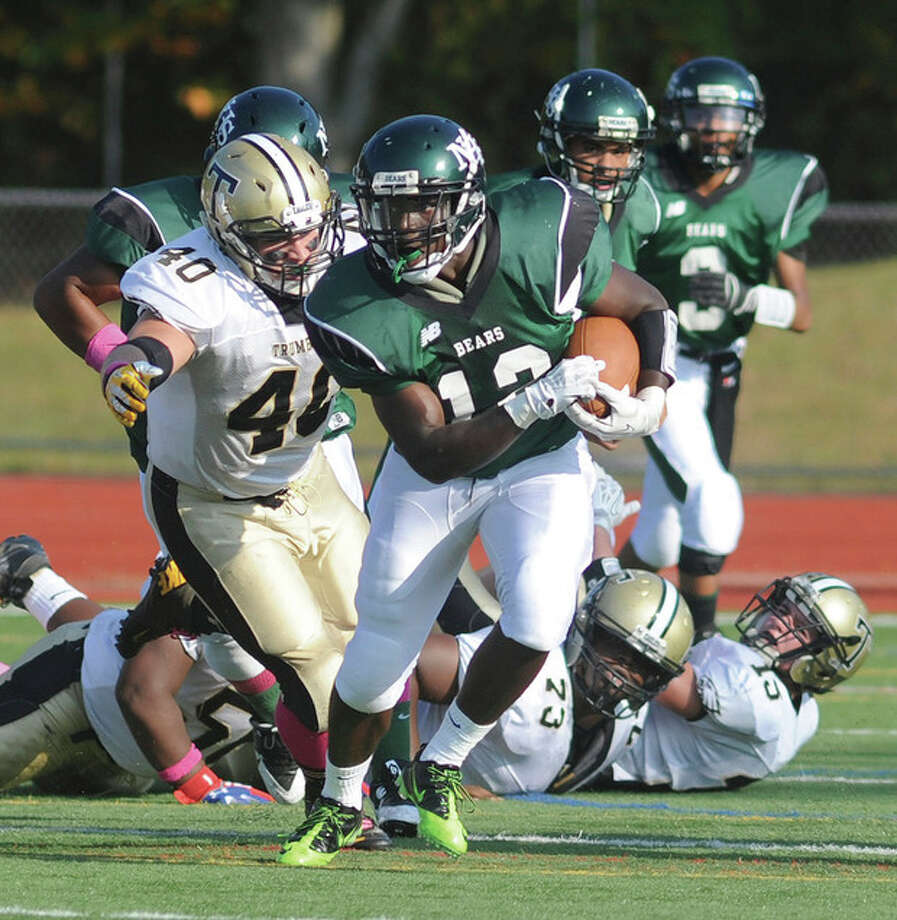 Hour photo/John NashUnder a bevy of eyes watching him, Norwalk's Clifford Joseph, center, runs away from blockers and tacklers alike while gaining some ground in the first quarter of Saturday's game against Trumbull at Testa Field in Norwalk.