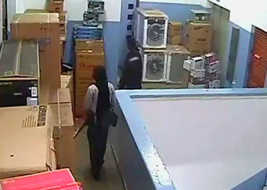In this video image released by the Kenyan Defence Forces and made available by Citizen TV Friday Oct. 4 2013, men carrying automatic weapons and carrying bags are seen in the storeroom of the Nakumatt shop during the four-day-long siege at the Westgate Mall in Nairobi Kenya which killed more than 60 people last month. A Kenyan military spokesman has confirmed the names of four attackers as Abu Baara al-Sudani, Omar Nabhan, Khattab al-Kene, left, and Umayr. (AP Photo/ Kenyan Defence forces via Citizen TV) / CitizenTV