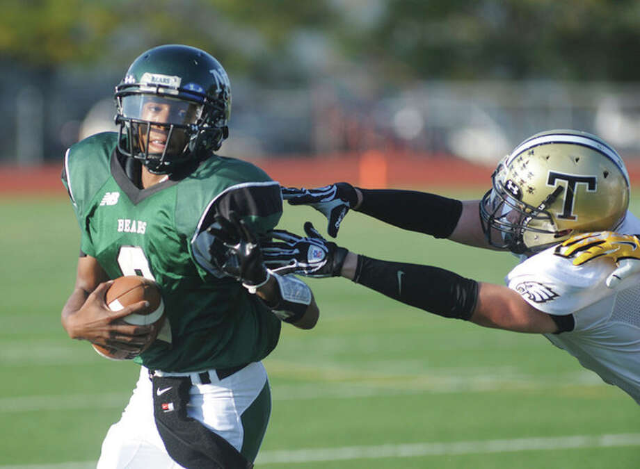 Hour photo/John NashNorwalk quarterback Jeremy Linton, left, avoids the diving tackle of a Trumbull defender on a second quarter run during Saturday's game at Testa Field in Norwalk. The visiting Eagles secured a 28-6 victory.
