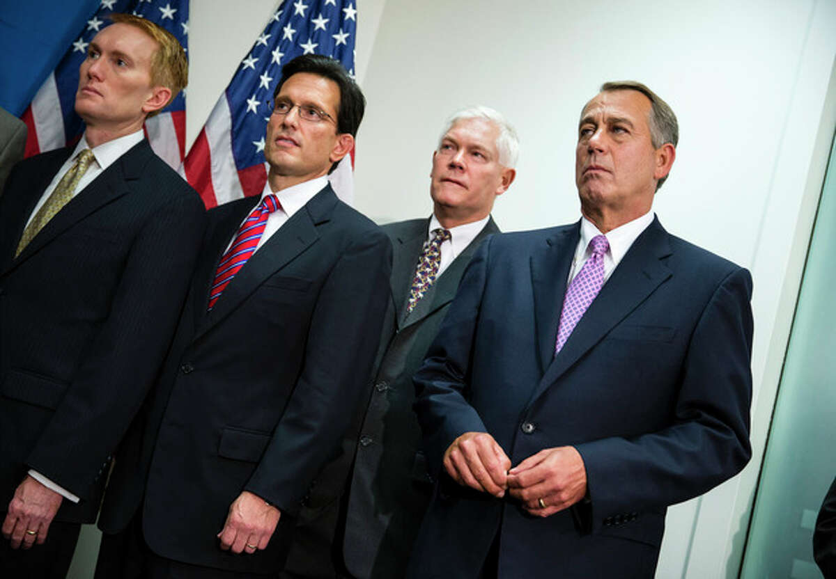 House Speaker John Boehner of Ohio, right, joined by members of the Republican Caucus, watches during a news conference on Capitol Hill in Washington, Friday, Oct. 4, 2013. From left are, Rep. James Lankford, R-Okla., House Majority Leader Eric Cantor of Va., Rep. Pete Sessions, R-Texas, and Boehner. Boehner is struggling between Democrats that control the Senate and GOP conservatives in his caucus who insist any funding legislation must also kill or delay the nation's new health care law. Added pressure came from President Barack Obama who pointedly blamed Boehner on Thursday for keeping federal agencies closed. (AP Photo/J. Scott Applewhite)
