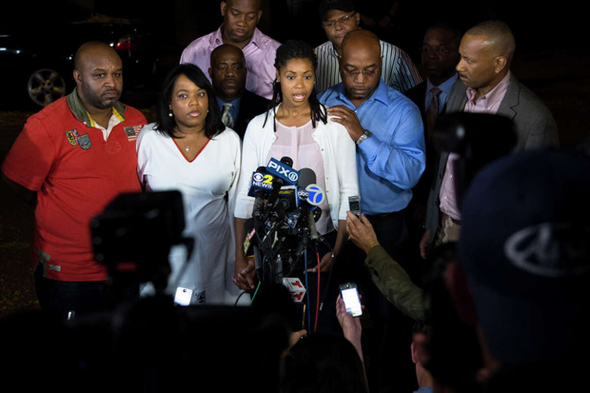 Amy Carey, center, sister of Miriam Carey, speaks to the media outside the home of her sister Valarie, second from left, in the Bedford-Stuyvesant neighborhood of Brooklyn, Friday, Oct. 4, 2013, in New York. Law-enforcement authorities have identified Miriam Carey, 34, as the woman who, with a 1-year-old child in her car, led Secret Service and police on a harrowing chase in Washington from the White House past the Capitol Thursday, attempting to penetrate the security barriers at both national landmarks before she was shot to death, police said. The child survived. (AP Photo/John Minchillo)