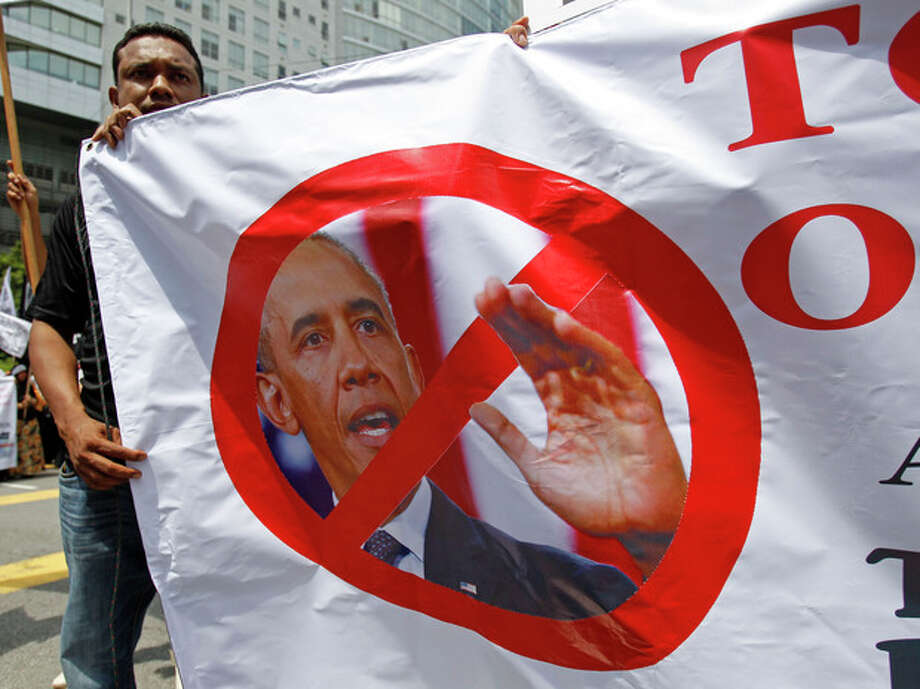 A Muslim protester holds a banner featuring a photo of U.S. President Barack Obama during a protest against the visit of Obama or Secretary of State John Kerry, scheduled for Oct. 11, outside the U.S. Embassy in Kuala Lumpur, Malaysia, Friday, Oct. 4, 2013. Obama is canceling a trip to Asia to stay in Washington and push for an elusive funding bill to get the nation's business back up and running. (AP Photo/Lai Seng Sin) / AP