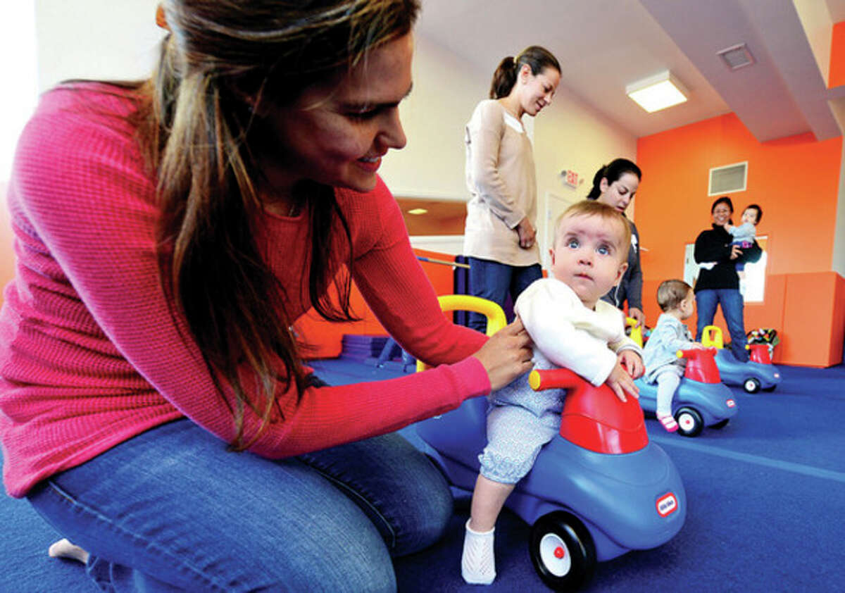 Claudia McKenna and her daughter Charlotte, 8 months, participate in a class at Kidsville in Westport as they announce the opening of their new 4,800 square foot facility at 1572 Post Road East. Hour photo / Erik Trautmann