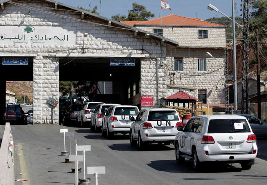 A convoy of inspectors from the Organization for the Prohibition of Chemical Weapons prepares cross into Syria at the Lebanese border crossing point of Masnaa, eastern Bekaa Valley, Lebanon, Tuesday, Oct. 1, 2013. An advance group of 20 inspectors from a Netherlands-based chemical weapons watchdog arrived in Syria on Tuesday to begin their complex mission of finding, dismantling and ultimately destroying an estimated 1,000-ton chemical arsenal. (AP Photo/Bilal Hussein) / AP