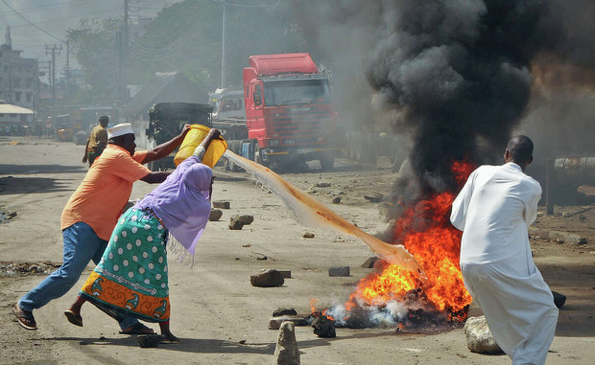 Residents throw water to put out the flames from burning tyres set on fire in a street by rioting youths, following Friday Muslim prayers in Mombasa, Kenya, Friday, Oct. 4, 2013. A religious leader on Kenya's coast says that the Muslim cleric Sheikh Ibrahim Ismael who preached at Mombasa's Masjid Musa Mosque, whose previous imam Aboud Rogo Mohammed was mysteriously shot dead in August 2012, has died in a barrage of bullets late Thursday near the coastal city of Mombasa. (AP Photo)
