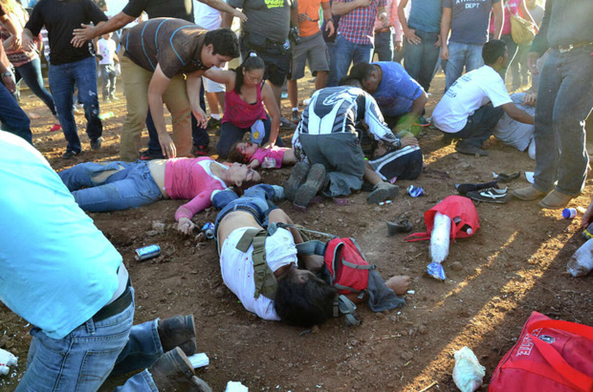 Injured people are treated after an out of control monster truck plowed through a crowd of spectators at a Mexican air show in the city of Chihuahua, Mexico, Saturday Oct. 5, 2013. According to authorities, at least 8 people were killed and 80 were injured. (AP Photo/El Diario de Chihuahua)