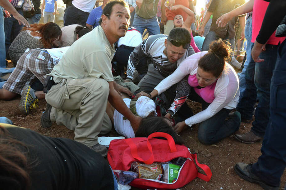 Injured people are treated after an out of control monster truck plowed through a crowd of spectators at a Mexican air show in the city of Chihuahua, Mexico, Saturday Oct. 5, 2013. According to authorities, at least 8 people were killed and 80 were injured. (AP Photo/El Diario de Chihuahua) / El Diario de Chihuahua