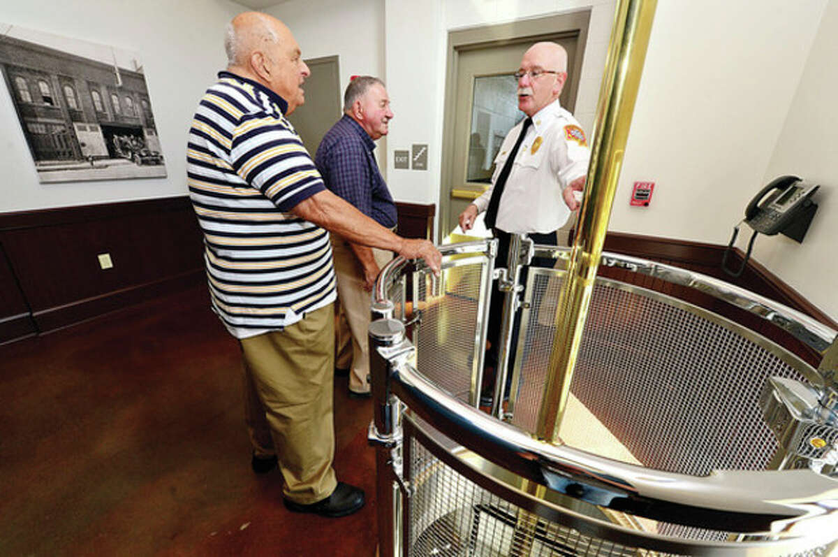 Hour photo / Erik Trautmann Chief Denis McCarthy points out the poles to former Norwalk firefighters Joseph Ferraro and Julius Oraviz as the City of Norwalk and the Fire Department formally dedicate the new Central Fire Station Saturday.