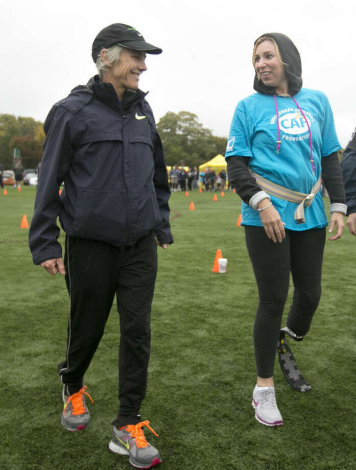 Two-time Boston Marathon winner Joan Benoit Samuelson, left, speaks with Heather Abbott, right, who lost part of her left leg in the 2013 Boston Marathon explosion, during a running clinic for challenged athletes Sunday, Oct. 6, 2013, in Cambridge, Mass. The clinic was run by the Challenged Athletes Foundation, which provides equipment and training for amputees to participate in sports. (AP Photo/Steven Senne)