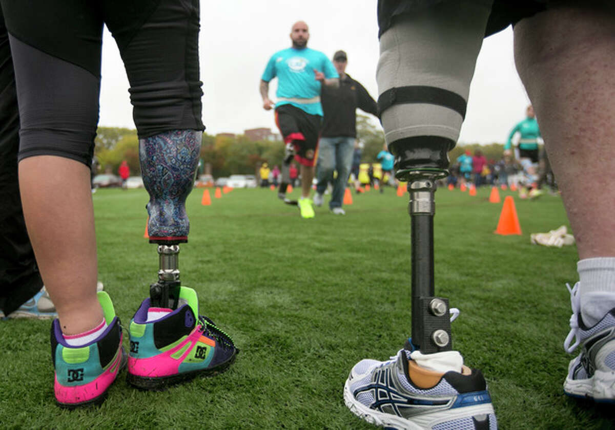 Andres Burgos, of Foxborough, Mass., top, runs toward Jordan Simpson, 14, of Berlin, Mass., legs only at left, and Jim Kane, of Mansfield, Mass., legs only at right, using a prosthetic leg during a running clinic for challenged athletes, in Cambridge, Mass., Sunday, Oct. 6, 2013. The clinic was run by the Challenged Athletes Foundation, which provides equipment and training for amputees to participate in sports. (AP Photo/Steven Senne)