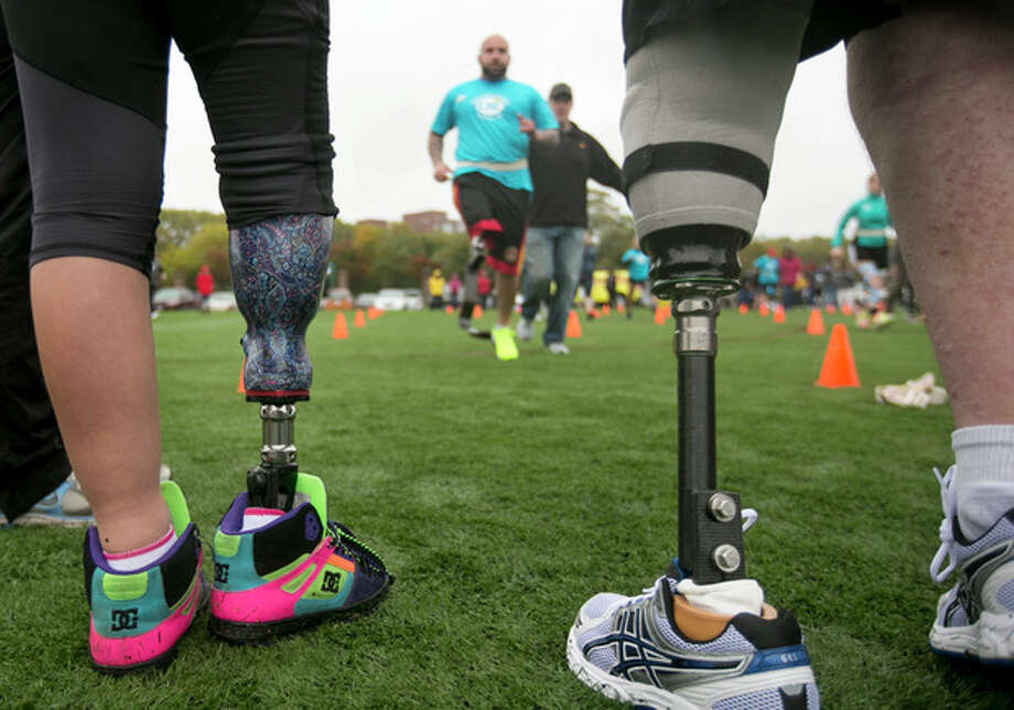 Andres Burgos, of Foxborough, Mass., top, runs toward Jordan Simpson, 14, of Berlin, Mass., legs only at left, and Jim Kane, of Mansfield, Mass., legs only at right, using a prosthetic leg during a running clinic for challenged athletes, in Cambridge, Mass., Sunday, Oct. 6, 2013. The clinic was run by the Challenged Athletes Foundation, which provides equipment and training for amputees to participate in sports. (AP Photo/Steven Senne) / AP