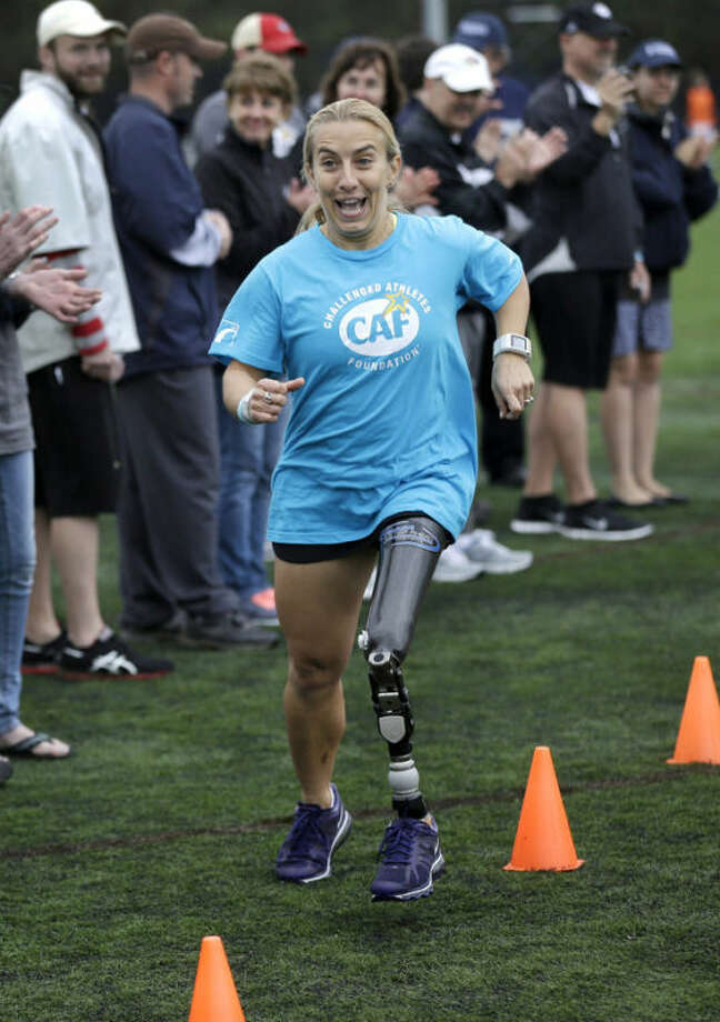 Triathlete Sarah Reinertsen, of San Juan Capistrano, Calif., smiles as she completes an obstacle course during a running clinic for challenged athletes Sunday, Oct. 6, 2013, in Cambridge, Mass. The clinic was run by the Challenged Athletes Foundation, which provides equipment and training for amputees to participate in sports. (AP Photo/Steven Senne)