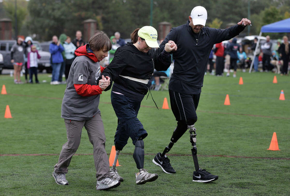 Celeste Corcoran, center, of Lowell, Mass., who lost her legs in the 2013 Boston Marathon explosion, is assisted by Ann-Marie Starck, of Ashford, Conn., left, and Gabriel Martinez, of Golden, Colo., right, during a running clinic for challenged athletes Sunday, Oct. 6, 2013, in Cambridge, Mass. In the clinic at Harvard University Sunday several victims of the April 15 explosions were trying to run on new prosthetic legs. (AP Photo/Steven Senne)