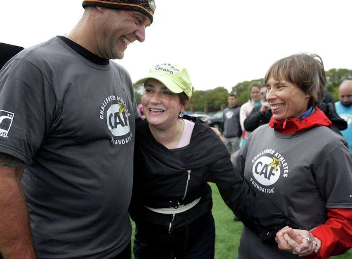 Celeste Corcoran, of Lowell, Mass., center, who lost her legs in the 2013 Boston Marathon explosion, celebrates with prosthetist Jerry Scandiffio, of Wakefield, Mass., left, and Ann-Marie Starck, of Ashford, Conn., right, after completing an obstacle course during a running clinic for challenged athletes Sunday, Oct. 6, 2013, in Cambridge, Mass. The clinic was run by the Challenged Athletes Foundation, which provides equipment and training for amputees to participate in sports. (AP Photo/Steven Senne)