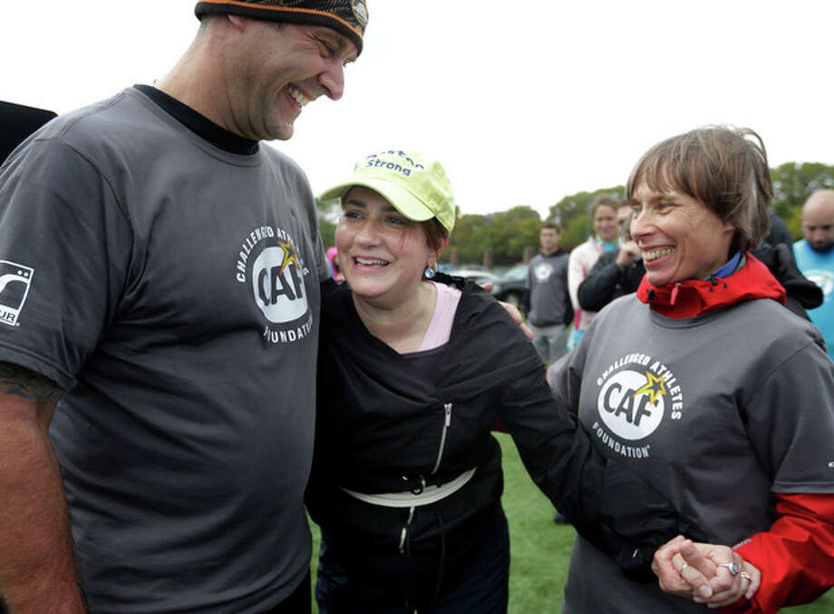 Celeste Corcoran, of Lowell, Mass., center, who lost her legs in the 2013 Boston Marathon explosion, celebrates with prosthetist Jerry Scandiffio, of Wakefield, Mass., left, and Ann-Marie Starck, of Ashford, Conn., right, after completing an obstacle course during a running clinic for challenged athletes Sunday, Oct. 6, 2013, in Cambridge, Mass. The clinic was run by the Challenged Athletes Foundation, which provides equipment and training for amputees to participate in sports. (AP Photo/Steven Senne) / AP