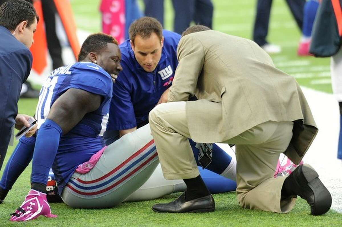 Trainers work on New York Giants defensive end Jason Pierre-Paul (90) during the first half of an NFL football game against the Philadelphia Eagles Sunday, Oct. 6, 2013, in East Rutherford, N.J. (AP Photo/Bill Kostroun)
