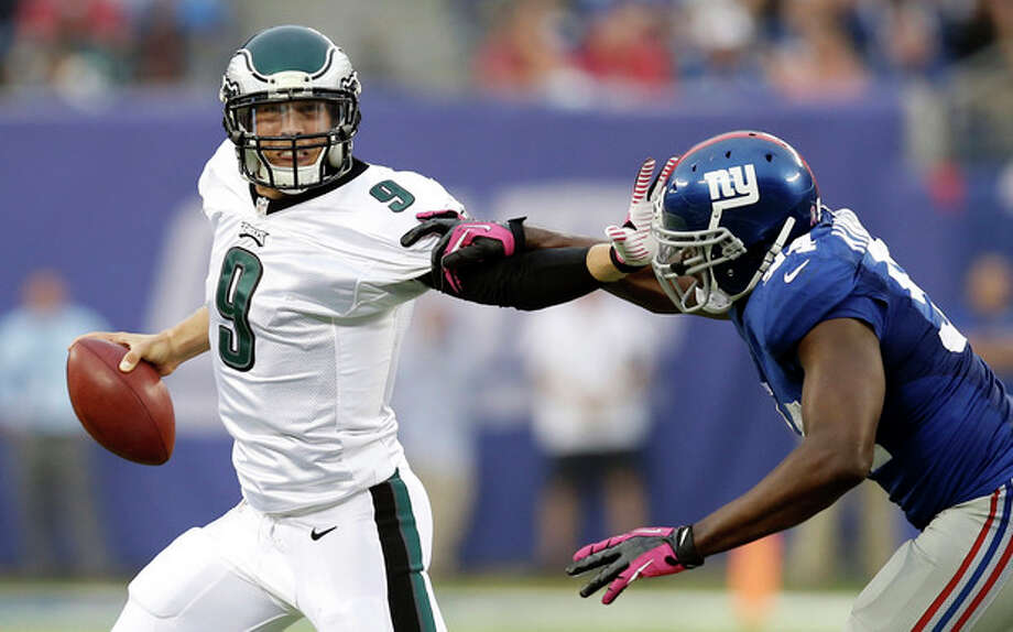Philadelphia Eagles' Nick Foles (9) stiff-arms New York Giants' Mathias Kiwanuka (94) during the second half of an NFL football game on Sunday, Oct. 6, 2013, in East Rutherford, N.J. (AP Photo/Kathy Willens) / AP