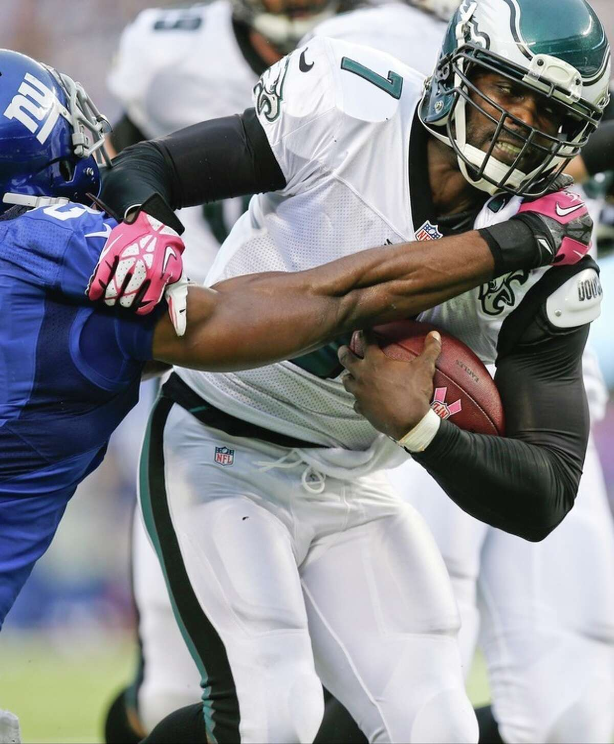 Philadelphia Eagles quarterback Michael Vick (7) fights off a tackle by New York Giants' Ryan Mundy during the first half of an NFL football game on Sunday, Oct. 6, 2013, in East Rutherford, N.J. (AP Photo/Kathy Willens)