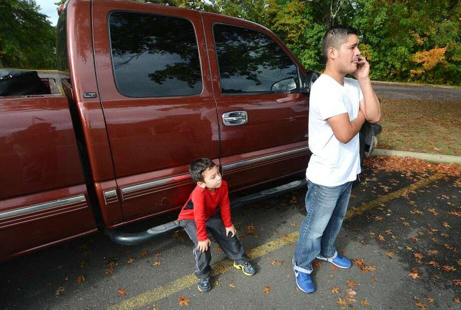 Hour Photo/Alex von Kleydorff Jorge Alvarado makes some phone calls after trying to drop off his nephew 4yr old Kendrick Leal at NEON Child Development Program on Monday morning. A sign posted at the Nathaniel Ely school stated it was closed Monday and Tuesday