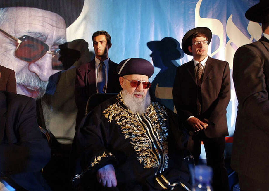 File - In this Dec. 5, 2002 file photo, Rabbi Ovadia Yosef sits surrounded by members of his staff during a rally of his Ultra-Orthodox Shas party in Jerusalem. Rabbi Ovadia, the religious scholar and spiritual leader of Israel's Sephardic Jews who transformed his downtrodden community of immigrants from North Africa and Arab nations and their descendants into a powerful force in Israeli politics, has died. He was 93.(AP Photo/Enric Marti, File) / AP