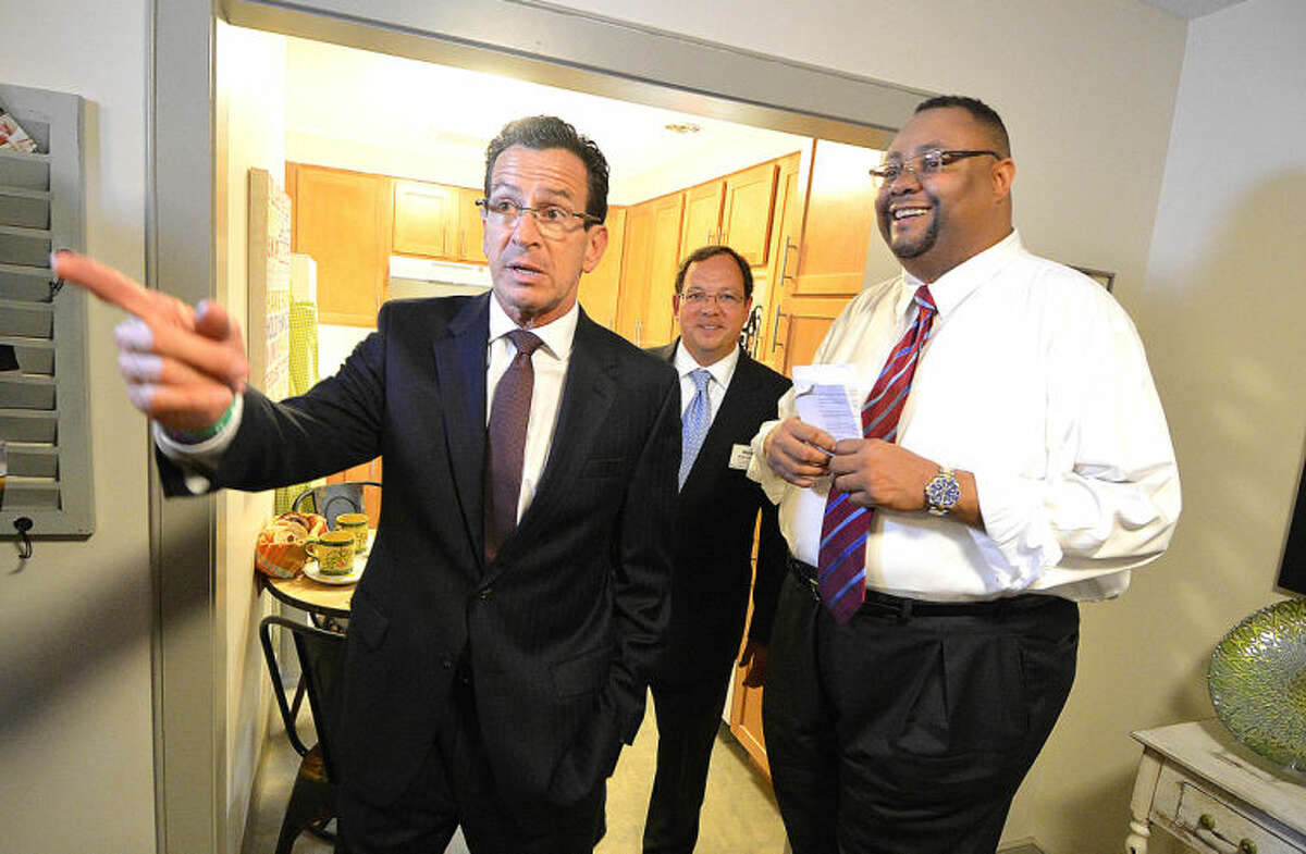 Hour Photo/Alex von Kleydorff . Alan Mathis, President and CEO Liberation Programs Inc along with Mike Matteo of United Health Group show a finished unit at Gini's House to Gov. Dan Malloy