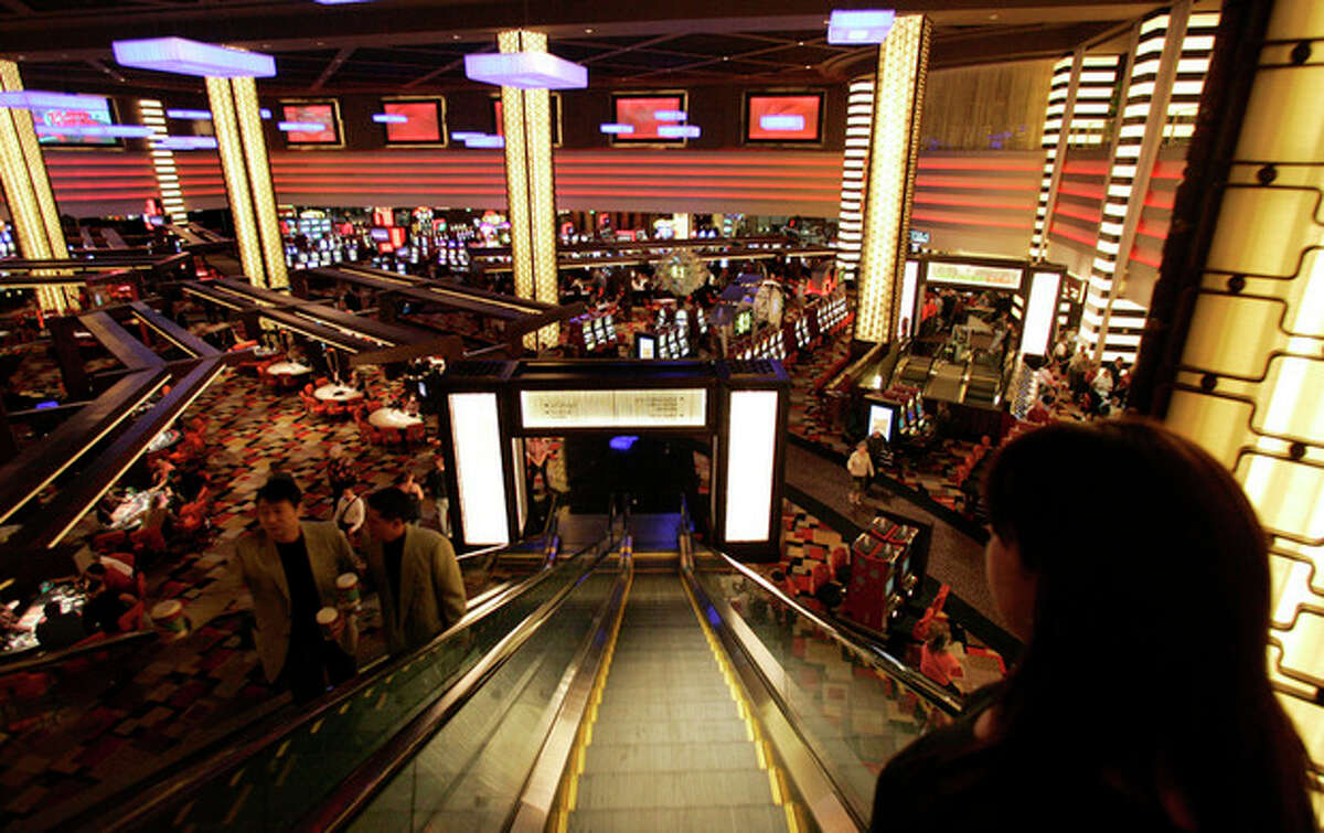 FILE - In this file photo taken Wednesday, Nov. 14, 2007, guests descend an escalator to the main casino floor of the Planet Hollywood Resort & Casino in Las Vegas. While casinos have thousands of cameras watching the gaming floors, entrances and some elevators, cameras are absent in the hallways of the guest room floors where thousands of crimes occur. (AP Photo/Jae C. Hong, File)
