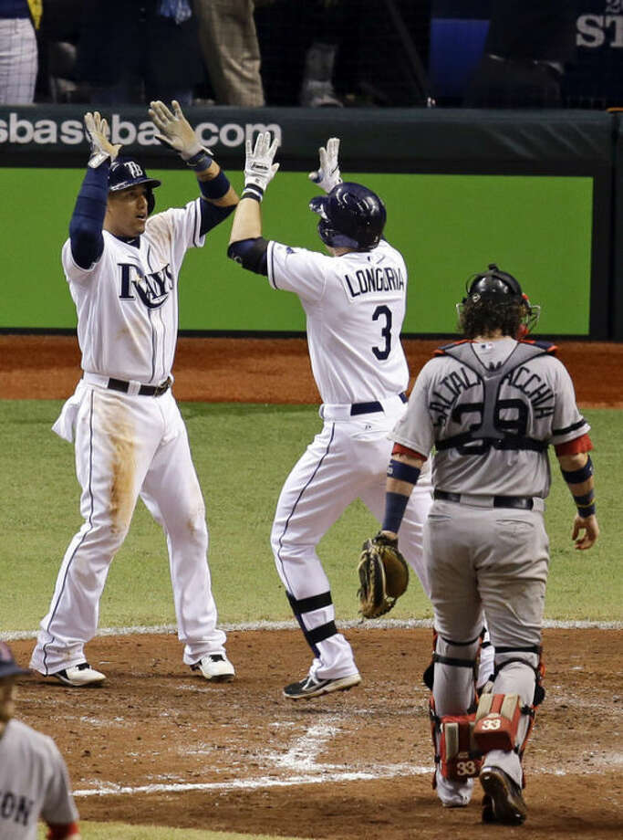 Tampa Bay Rays' Evan Longoria (3) celebrates his fifth inning three-run home run with teammate Yunel Escobar, left, as Boston Red Sox catcher Jarrod Saltalamacchia walks back to the batter's box during Game 3 of an American League baseball division series in St. Petersburg, Fla., Monday, Oct. 7, 2013. (AP Photo/John Raoux)