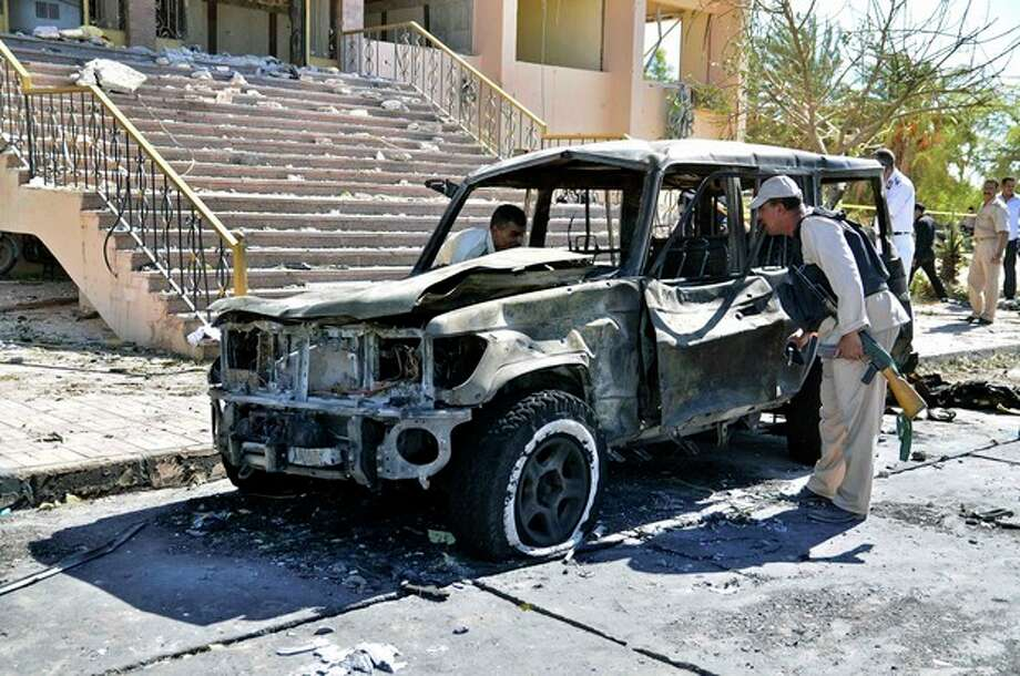 Egyptian security forces inspect the site of a suicide car bombing on a security headquarters in the southern Sinai town of el-Tor, Egypt, Monday, Oct. 7, 2013. The explosion in el-Tor killed several policemen and wounded tens of others, signaling what could be the spread of attacks by Islamic militants, already active in northern Sinai. (AP Photo/Mostafa Darwish) / AP