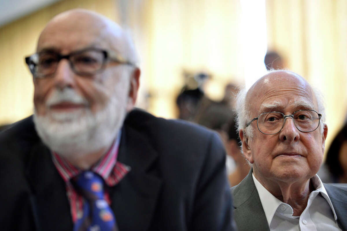 FILE - In this Wednesday, July 4, 2012 file photo Belgium physicist Francois Englert, left, and British physicist Peter Higgs right, answer journalist's questions at the European Organization for Nuclear Research (CERN) in Meyrin near Geneva, Switzerland. Francois Englert and Peter Higgs were awarded the Nobel physics prize on Tuesday Oct. 8, 2013. (AP Photo/Keystone/Martial Trezzini, File)