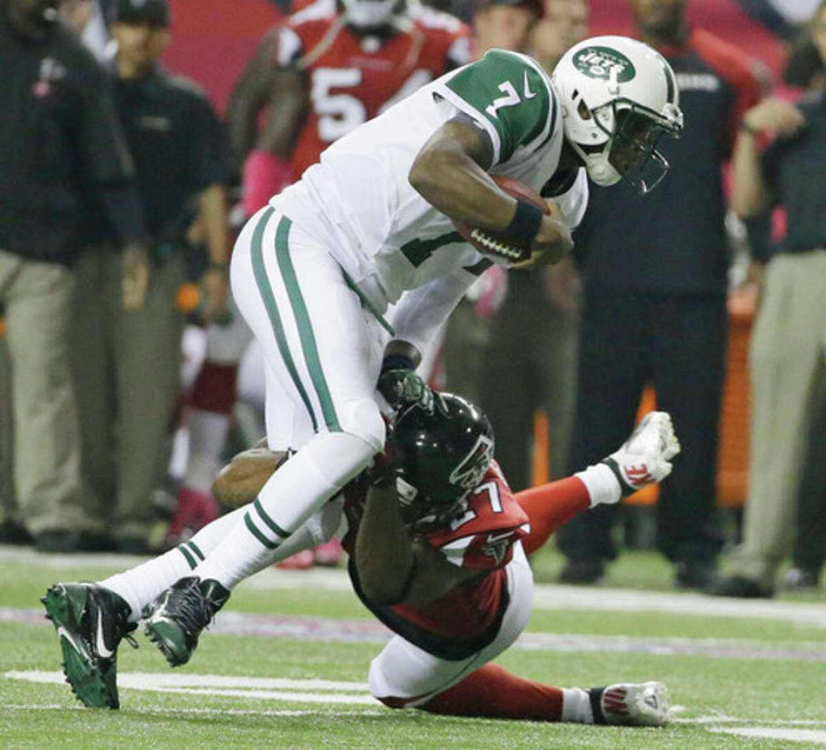 New York Jets quarterback Geno Smith (7) his hit in the open field by Atlanta Falcons cornerback Robert McClain (27) during the second half of an NFL football game, Monday, Oct. 7, 2013, in Atlanta. (AP Photo/David Goldman)