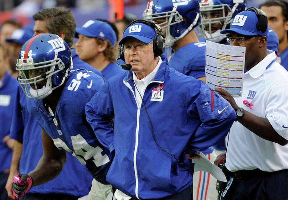 New York Giants head coach Tom Coughlin, center, watches his team play during the first half of an NFL football game against the Philadelphia Eagles, Sunday, Oct. 6, 2013, in East Rutherford, N.J. (AP Photo/Bill Kostroun) / FR51951 AP