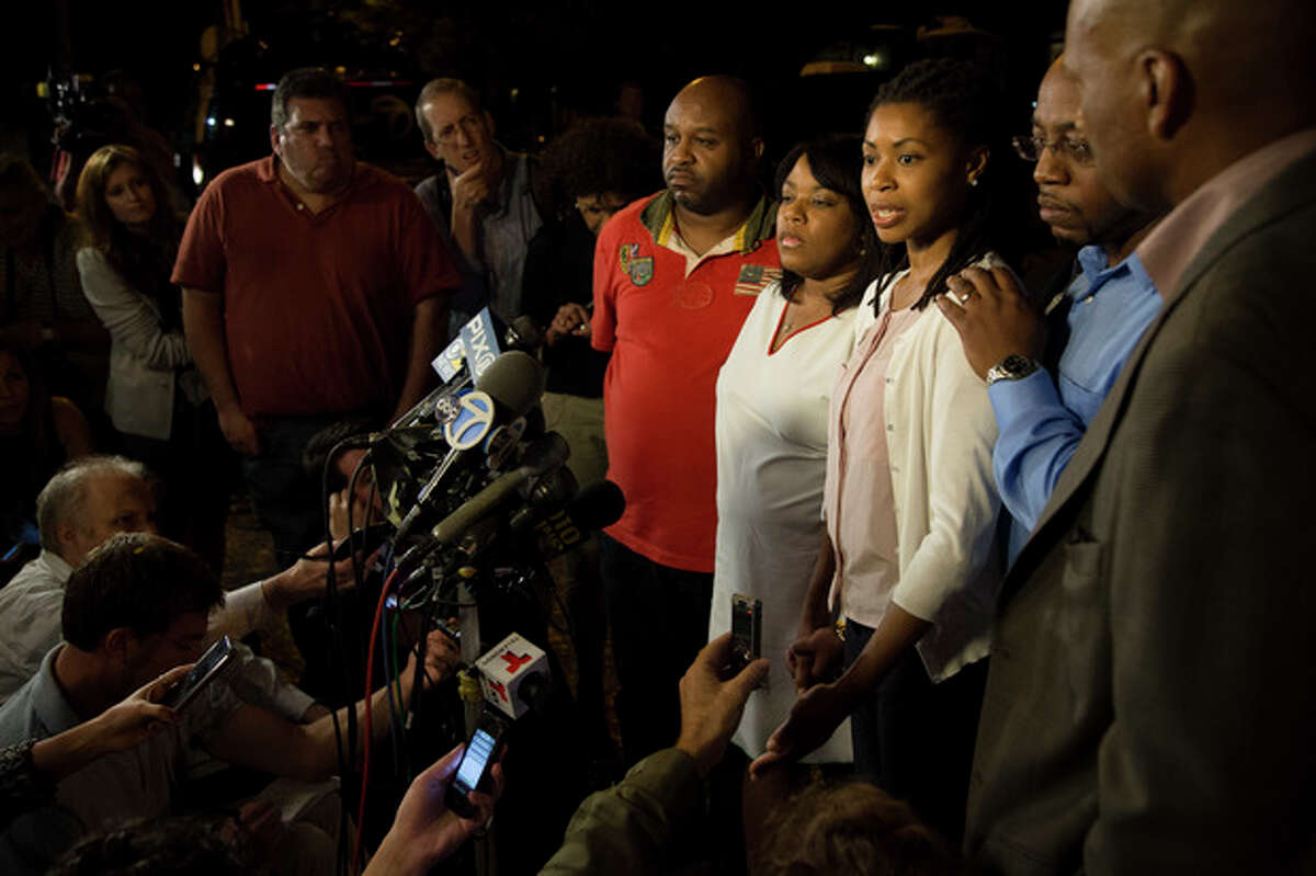 CORRECTS AMY CAREY TO AMY CAREY-JONES - Amy Carey-Jones, sister of Miriam Carey, speaks outside the home of her sister Valarie, fourth from right, in the Bedford-Stuyvesant neighborhood of Brooklyn, Friday, Oct. 4, 2013, in New York. Law-enforcement authorities have identified Miriam Carey, 34, as the woman who, with a 1-year-old child in her car, led Secret Service and police on a harrowing chase in Washington from the White House past the Capitol Thursday, attempting to penetrate the security barriers at both national landmarks before she was shot to death, police said. The child survived. (AP Photo/John Minchillo)