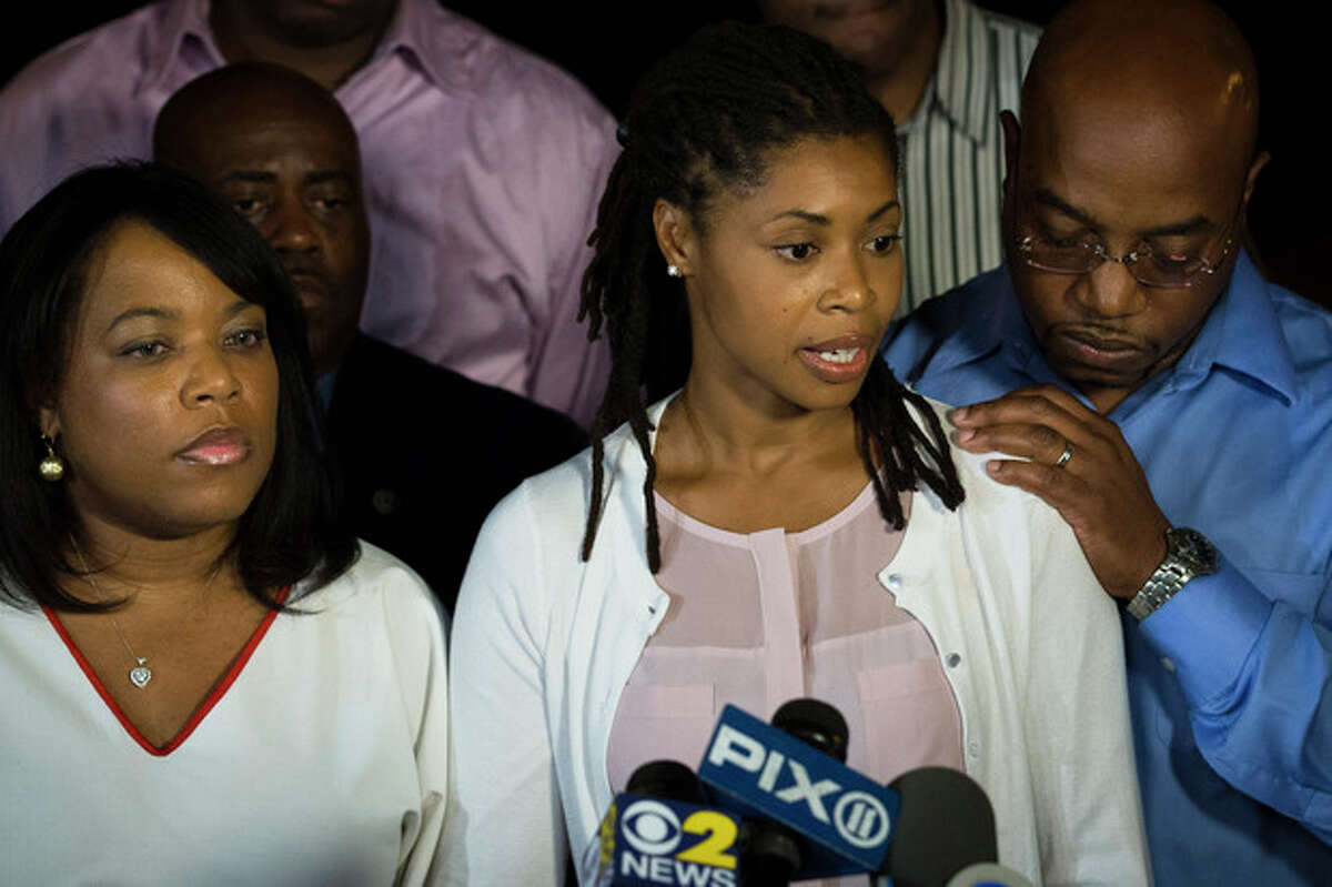 CORRECTS AMY CAREY TO AMY CAREY-JONES - Amy Carey-Jones, center, sister of Miriam Carey, speaks to the media outside the home of her sister Valarie, left, in the Bedford-Stuyvesant neighborhood of Brooklyn, Friday, Oct. 4, 2013, in New York. Law-enforcement authorities have identified Miriam Carey, 34, as the woman who, with a 1-year-old child in her car, led Secret Service and police on a harrowing chase in Washington from the White House past the Capitol Thursday, attempting to penetrate the security barriers at both national landmarks before she was shot to death, police said. The child survived. (AP Photo/John Minchillo)