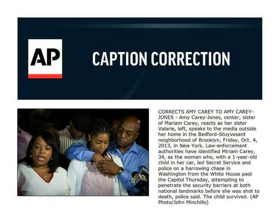 CORRECTS AMY CAREY TO AMY CAREY-JONES - Amy Carey-Jones, center, sister of Mariam Carey, reacts as her sister Valarie, left, speaks to the media outside her home in the Bedford-Stuyvesant neighborhood of Brooklyn, Friday, Oct. 4, 2013, in New York. Law-enforcement authorities have identified Miriam Carey, 34, as the woman who, with a 1-year-old child in her car, led Secret Service and police on a harrowing chase in Washington from the White House past the Capitol Thursday, attempting to penetrate the security barriers at both national landmarks before she was shot to death, police said. The child survived. (AP Photo/John Minchillo) / FR170537 AP