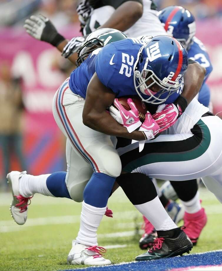 New York Giants' David Wilson (22) breaks a tackle by Philadelphia Eagles' DeMeco Ryans for a touchdown during the first half of an NFL football game Sunday, Oct. 6, 2013, in East Rutherford, N.J. (AP Photo/Kathy Willens) / AP