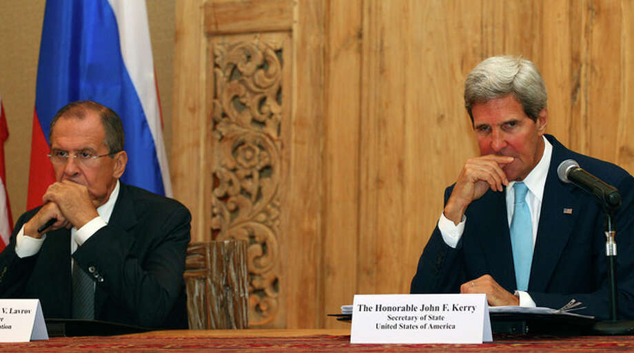 """U.S. Secretary of State John Kerry and Russian Foreign Minister Sergey Lavrov listen to a question by a journalist during a joint press conference on the sidelines of the Asia-Pacific Economic Cooperation (APEC) summit in Bali, Indonesia, Monday, Oct. 7, 2013. Kerry said that the United States and Russia are """"very pleased"""" with the progress made so far in destroying Syria's chemical weapons stocks. (AP Photo/Firdia Lisnawati) / AP"""